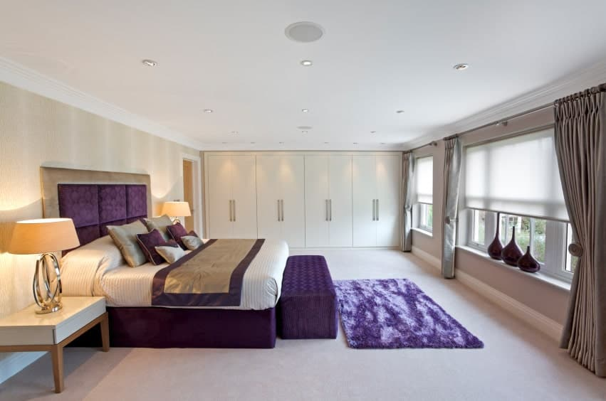 Purple bed, bench and area rug stands out in this beige primary bedroom with floor to ceiling wardrobes and glazed windows covered in roller blinds and blackout drapes.