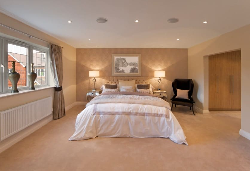 Ambient light from the table lamps create a warm and romantic vibe in this primary bedroom with a wingback chair and tufted bed placed against the beige walls clad in patterned wallpaper.