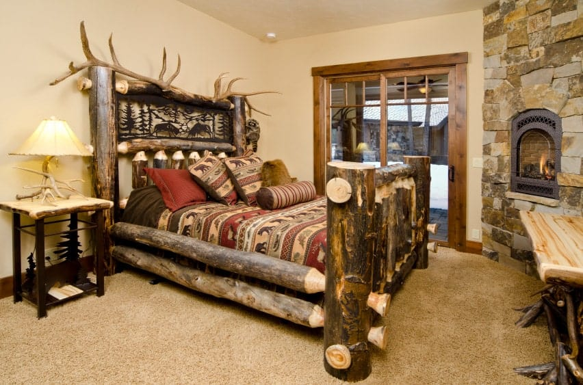 Rustic bedroom boasts a marvelous log bed with a driftwood decor on top complementing with the table lamp. It includes a wooden desk and an arched fireplace fitted on the stone brick corner wall.