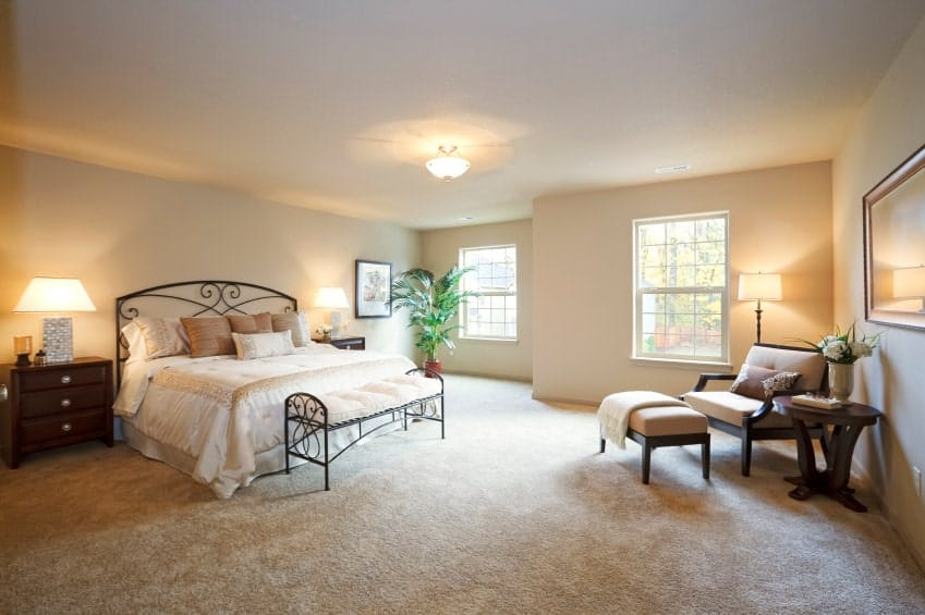 Beige bedroom with a cushioned lounge chair and ornate metal bed paired with a matching bench over carpet flooring. It is illuminated by a semi-flush mount light and table lamps that sit on dark wood nightstands.