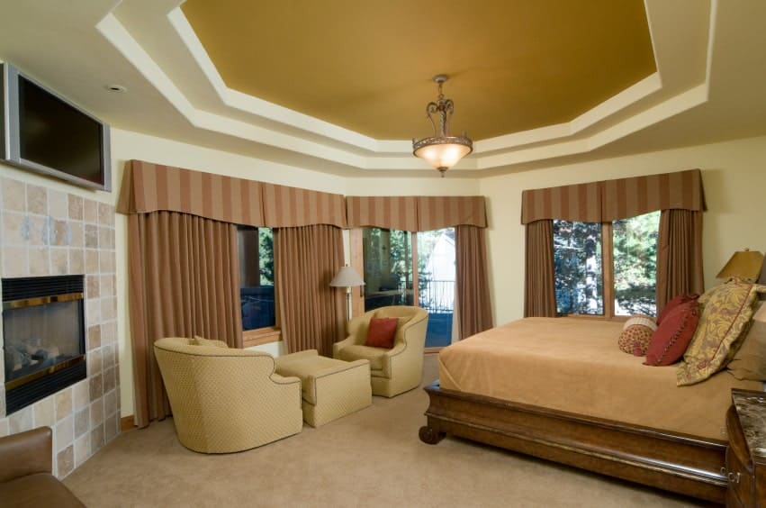 This primary bedroom showcases a glass enclosed fireplace and a wooden bed lighted by a fancy semi- flush mount light. It has a tray ceiling and glazed windows covered in blackout drapes and striped valances.
