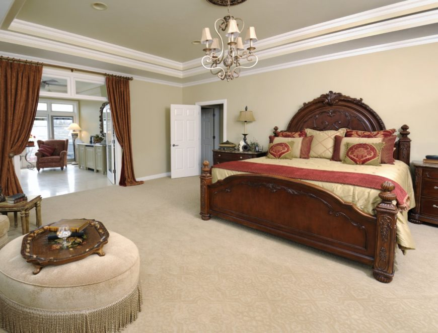 Classy bedroom with a carved wood bed and a seating area covered in brown draperies. It is illuminated by a gorgeous ornate chandelier that hung from the tray ceiling.
