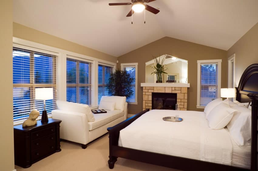 This primary bedroom offers a brick fireplace and dark wood bed facing the white upholstered bench against the glazed windows. It has carpet flooring and cathedral ceiling mounted with a fan.