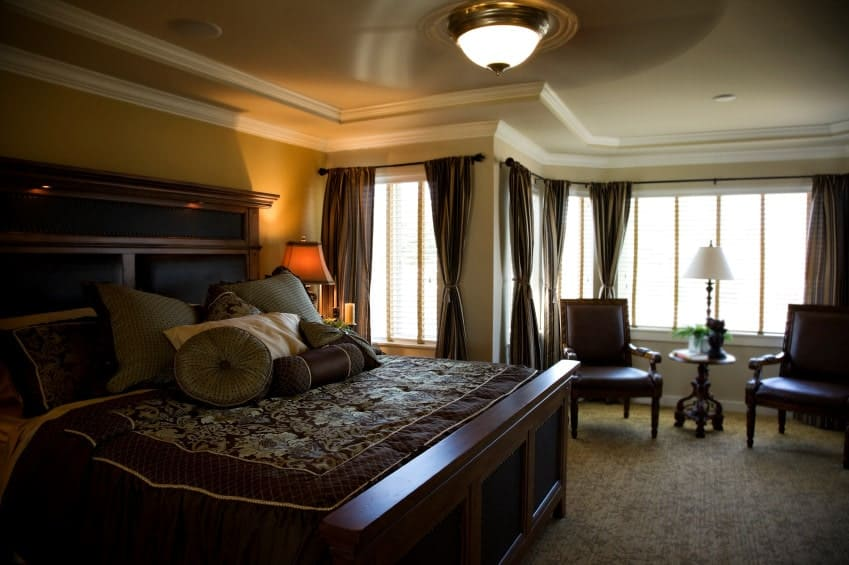Dark primary bedroom filled with wooden furniture and a dome flush light mounted on the tray ceiling. It has carpet flooring and glass paneled windows covered in brown sheer curtains.