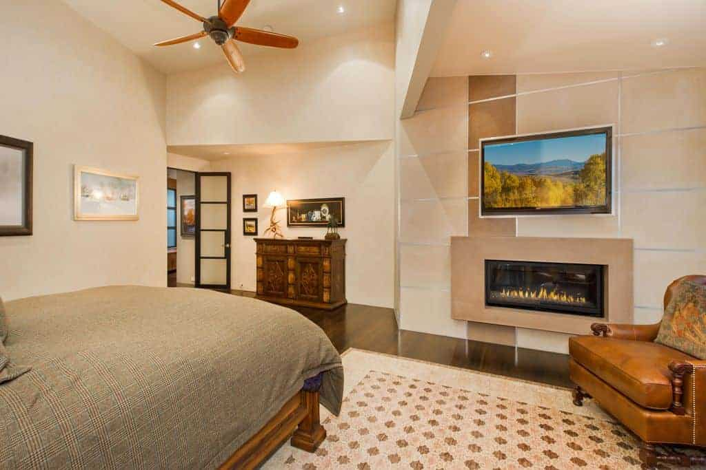 Beige primary bedroom showcases a wooden bed and brown leather armchair situated near the rectangular fireplace and flat screen TV that are mounted on the paneled wall.