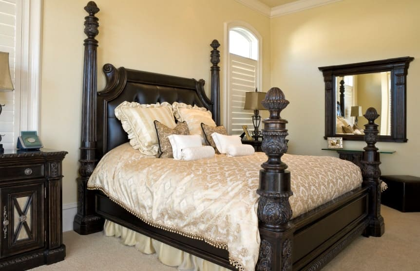 A four poster bed dressed in classy silk bedding complements the carved wood nightstands and dark wood framed mirror that hung above the glass top console table.