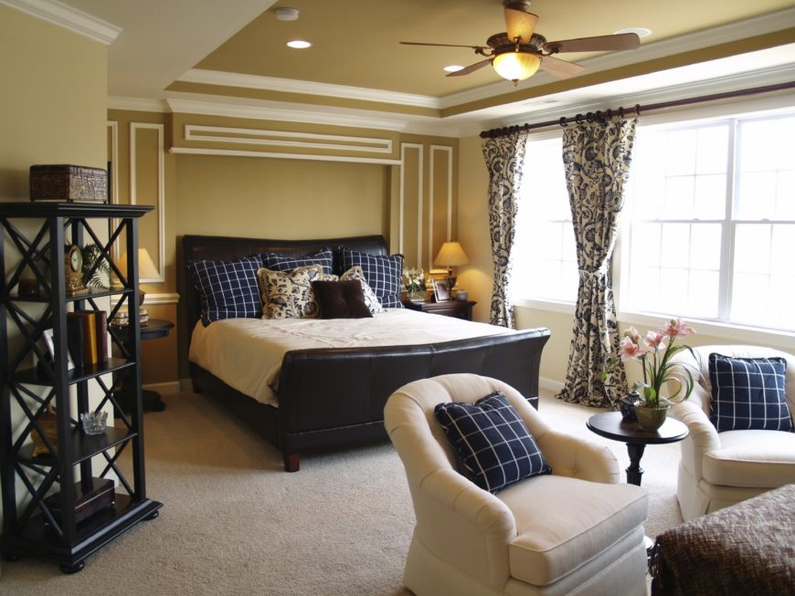 Beige primary bedroom boasts a black leather bed and round back armchairs accented with deep blue checkered pillows. It includes a shelving unit that complements the dark wood nightstands.