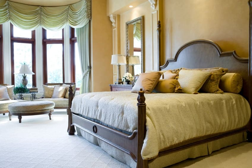 Sophisticated primary bedroom with a wooden bed and cozy seats paired with a round ottoman. It has textured carpet flooring and full height windows dressed in classy mint green drapes and valances.