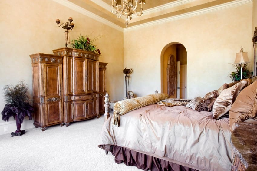 A carved wood wardrobe faces the skirted bed lighted by a brass chandelier that hung from the tray ceiling. This room has carpet flooring and an arched doorway that leads to the bathroom.