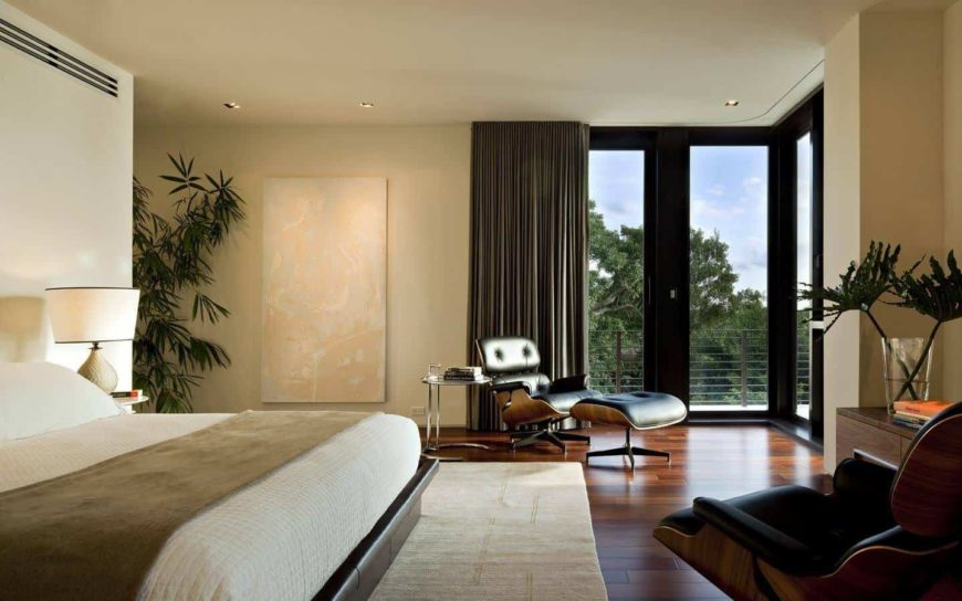 Fresh primary bedroom with black leather lounge chairs and a platform bed that sits on a beige area rug over wide plank flooring. It has full height glazing that overlooks the enchanting forest.