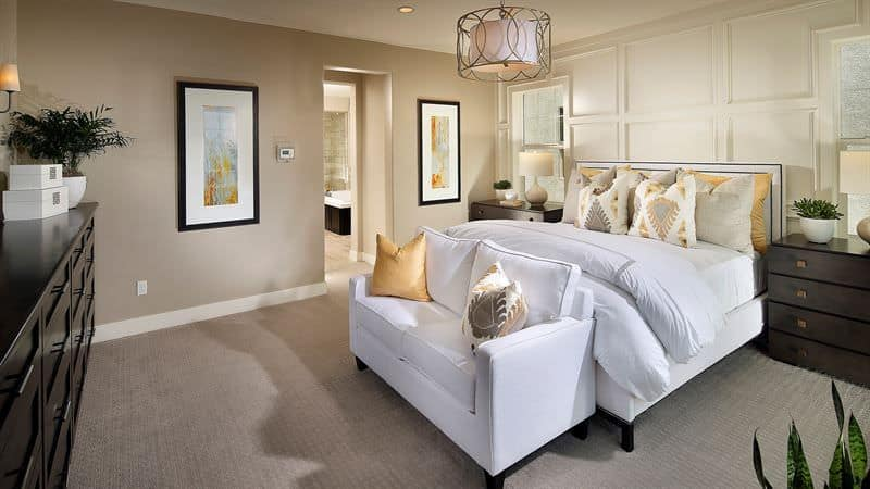A stylish drum pendant light illuminates this beige primary bedroom boasting white bed and loveseat contrasted by dark wood nightstands and dresser.