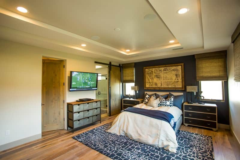 This bedroom features vintage artwork and a cozy bed flanked by nightstands and picture windows. It has a deep blue accent wall and a tray ceiling mounted with recessed lights.