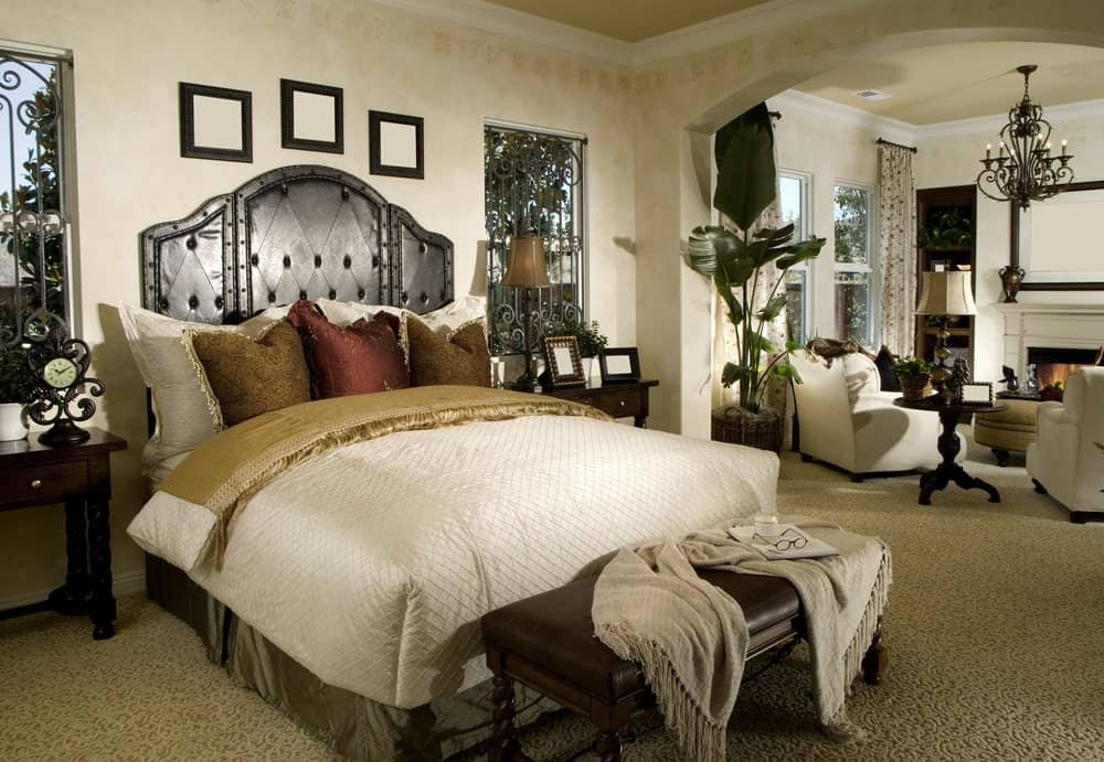 A brown leather bench sits in front of the skirted bed in this primary bedroom offering a seating area by the fireplace lighted by a traditional floor lamp and an ornate chandelier.