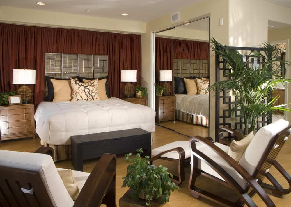 Burgundy drapes set a classy backdrop to the stylish bed accompanied by wooden nightstands and storage bench. It includes white lounge chairs and a built-in wardrobe with glass doors that create a large visual space to the room.
