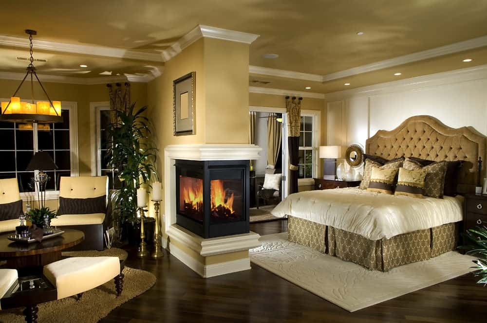 Warm primary bedroom with cozy rugs and triple sided fireplace that serves as a divider to the tufted bed and seating area. It is illuminated by a vintage chandelier and recessed ceiling lights.