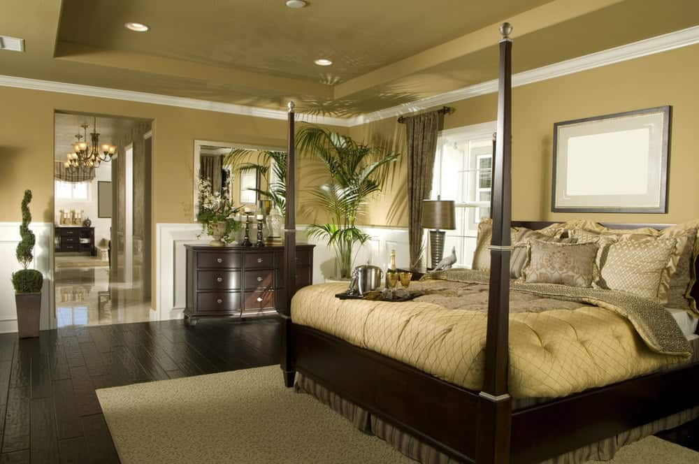 Beige bedroom furnished with dark wood dresser and four poster bed that sits on a textured area rug. It has wide plank flooring and tray ceiling mounted with recessed lights.