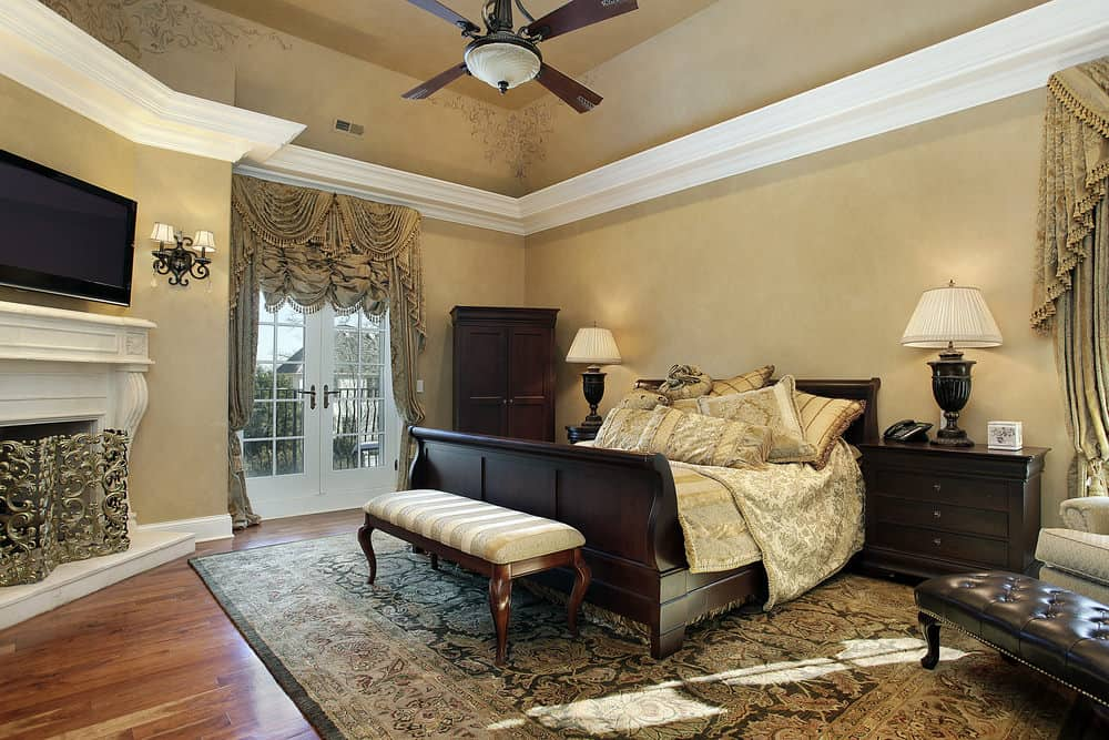 Luxury bedroom features a wooden bed with a stripe cushioned bench on its end along with a white fireplace covered with an ornate fence.