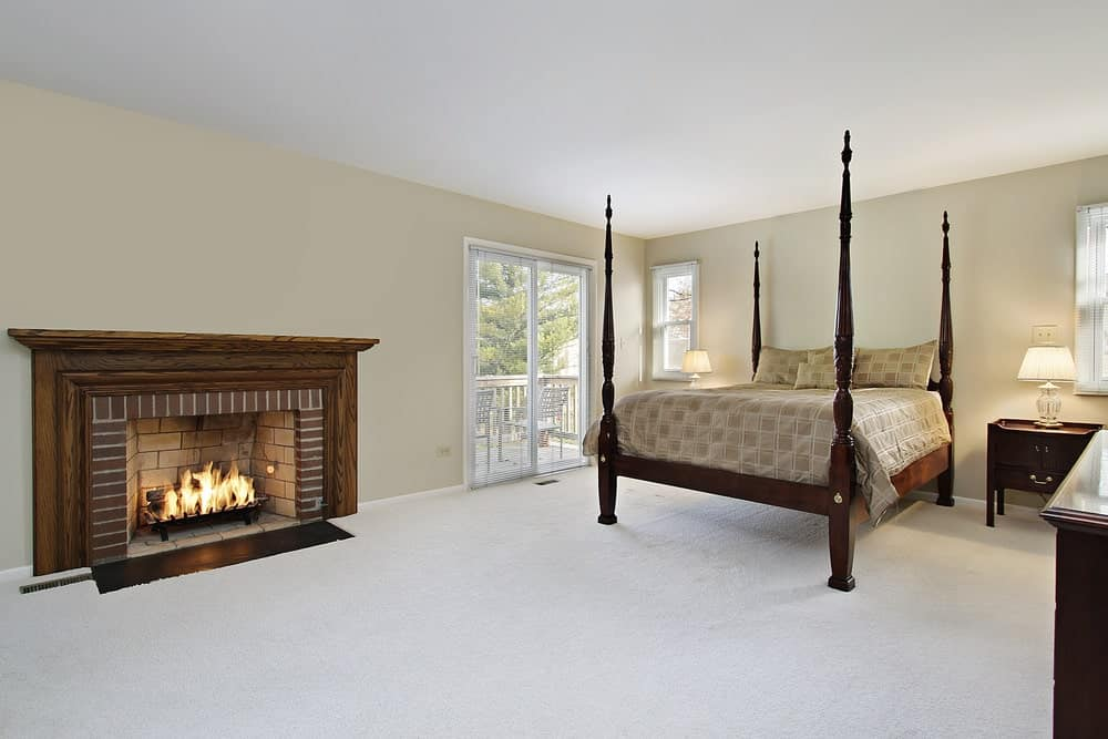 Simple bedroom with a four poster bed and a brick fireplace framed in a natural wood mantel. It has carpet flooring and glass slider leading out to the balcony.