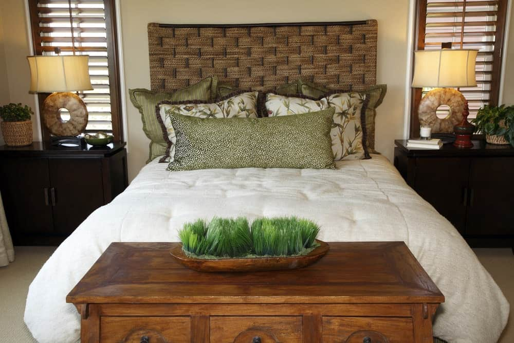 Lovely round table lamps sit on dark wood nightstands in this primary bedroom featuring a comfy bed with custom headboard. It includes a storage bench and glazed windows covered with wooden shutters.