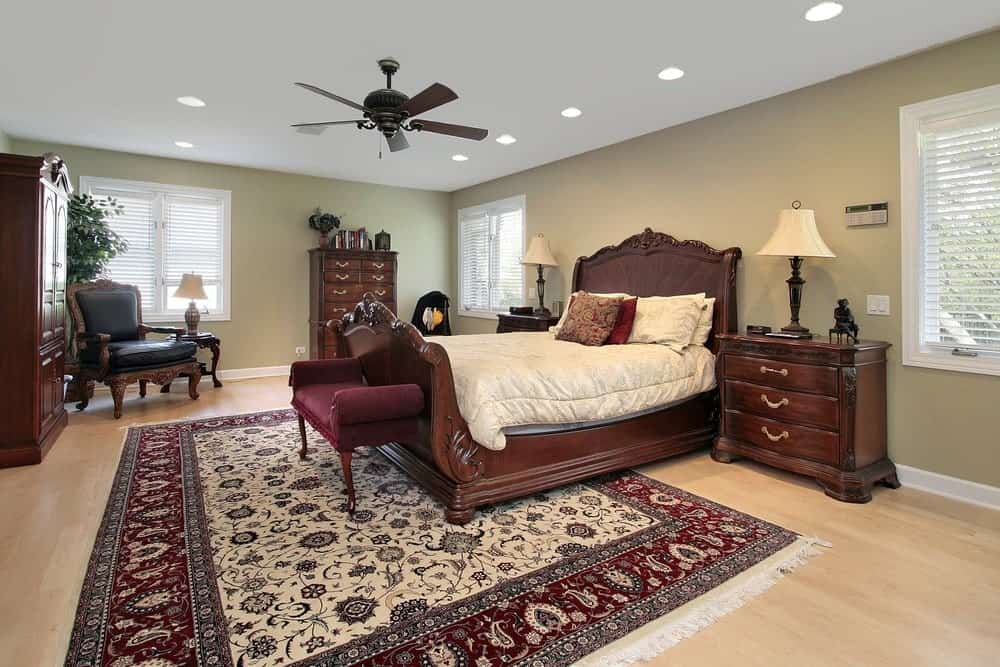 This primary bedroom showcases wooden cabinets and bed paired with a red upholstered bench that sits on a tasseled area rug over the light hardwood flooring.