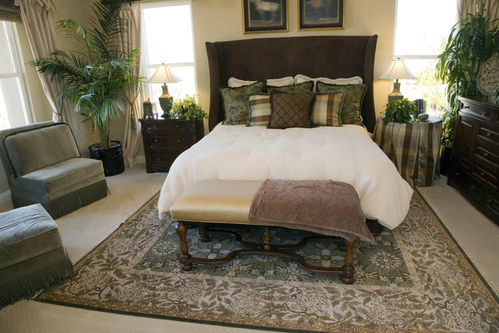 Tropical bedroom showcases green velvet chairs and brown wingback bed with a cushioned bench on its end over a foliage rug. It includes potted plants and framed artworks mounted on the beige wall.