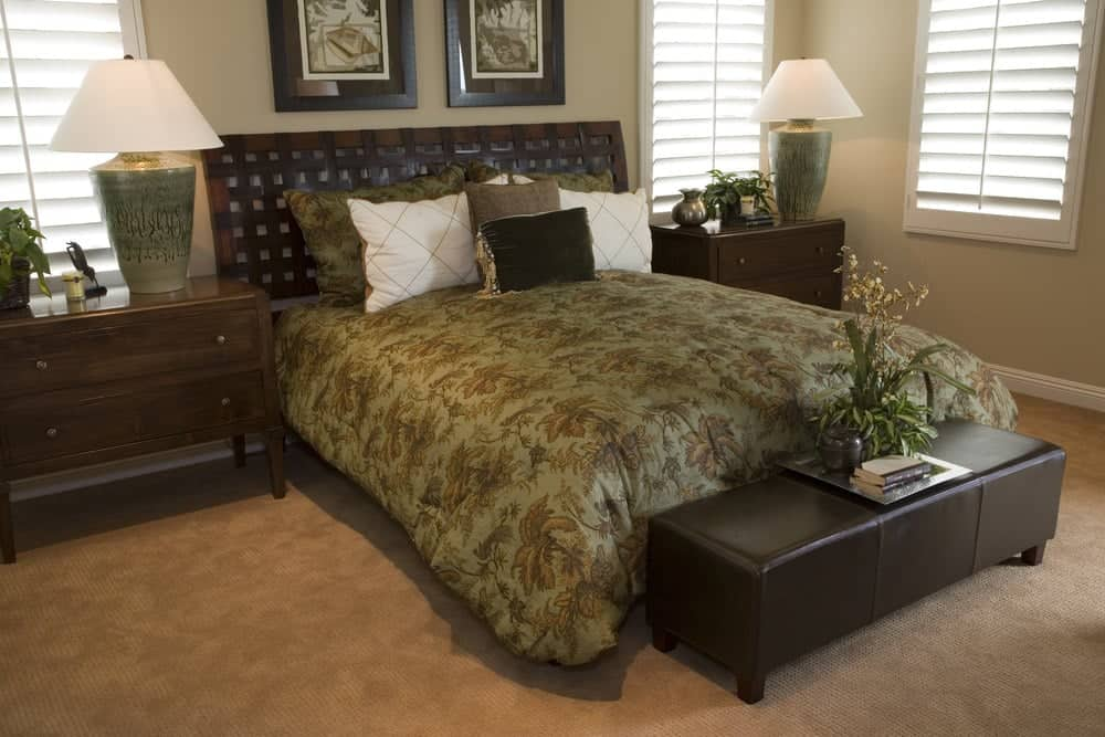 A pair of interesting wall arts hang above the wooden bed wrapped in a green floral duvet. This room boasts a black leather bench and two drawer nightstands topped with table lamps.