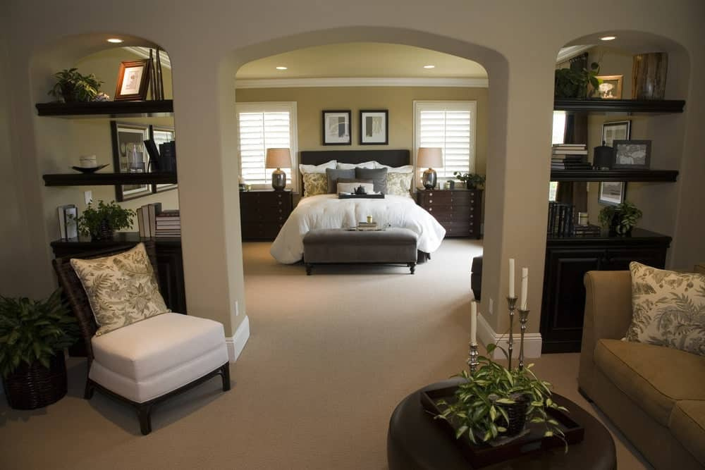 Beige primary bedroom with a gray upholstered bed and a seating area over carpet flooring. There's an open archway in the middle flanked by built-in shelvings.