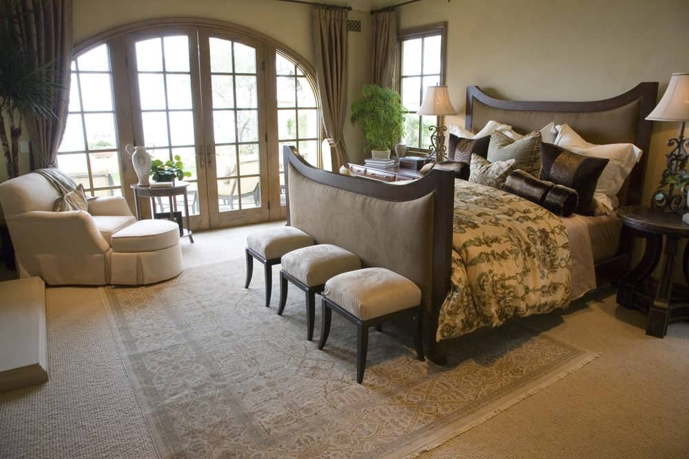 Fresh bedroom with carpet flooring and a French door leading out to the patio. It includes a velvet bed and white skirted lounge chair paired with a round side table.