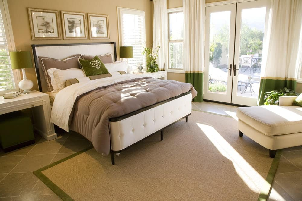 Beige primary bedroom with subtle green accents from the lampshades, pillow and drapes covering the French door. It has a white chaise lounge and bed that sit on a jute rug and limestone flooring.