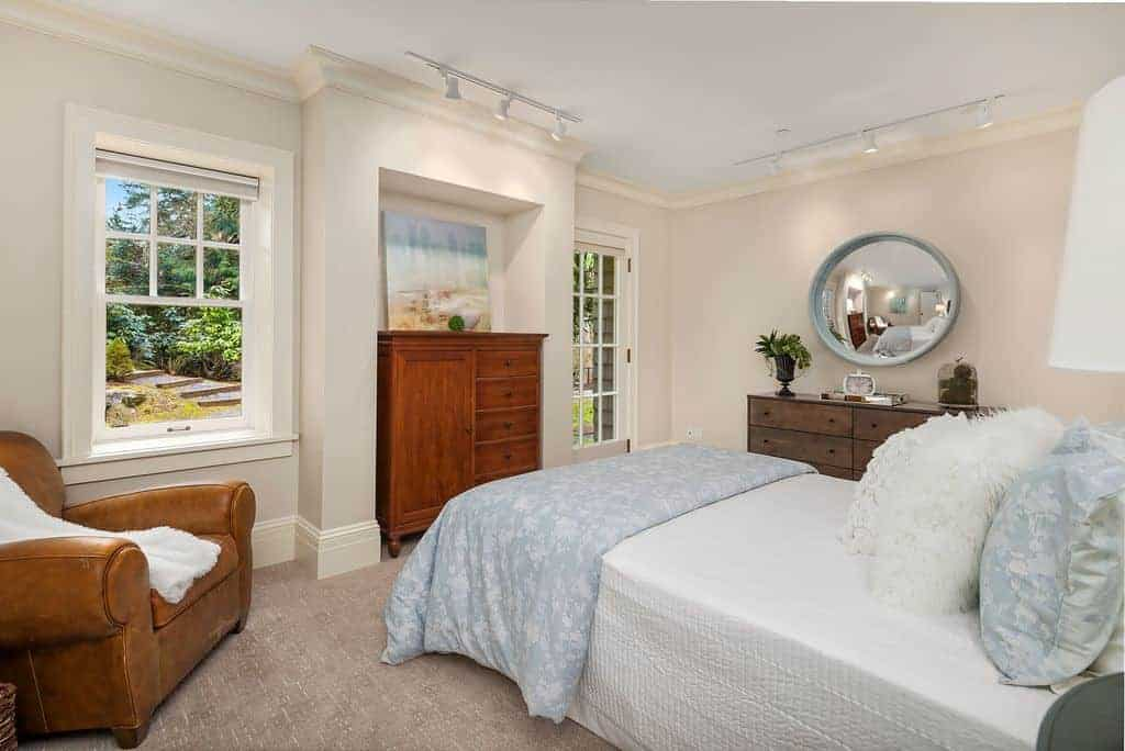 Airy bedroom decorated with a round concave mirror and lovely artwork that are illuminated by white track lights. It has a brown leather armchair and a comfy bed filled with fluffy and furry pillows.
