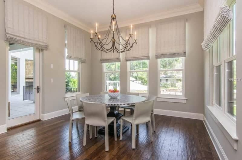 A spacious dining area with a round dining table set lighted by a chandelier and is set on the home's hardwood flooring.
