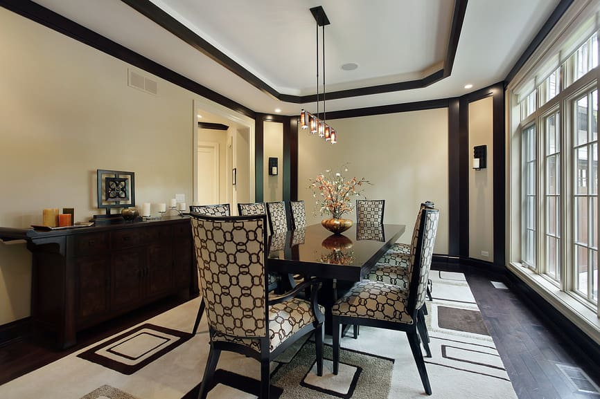 Large dining room featuring a classy set of seats and a black dining table set lighted by fancy ceiling lighting hanging from the stylish tray ceiling.