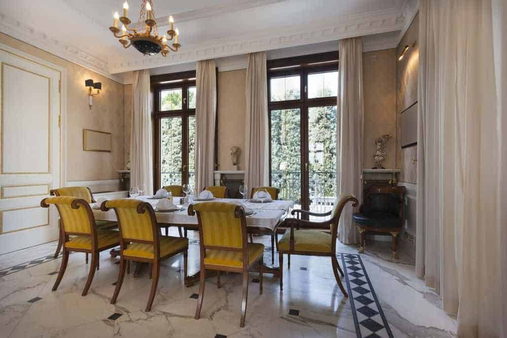 A large dining room boasting a magnificent ceiling and stunning flooring. The room offers a classy dining table and chairs set surrounded by elegantly decorated walls.