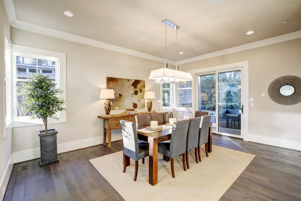 A spacious dining room boasting a classy dining table set on top of an area rug covering the hardwood flooring.