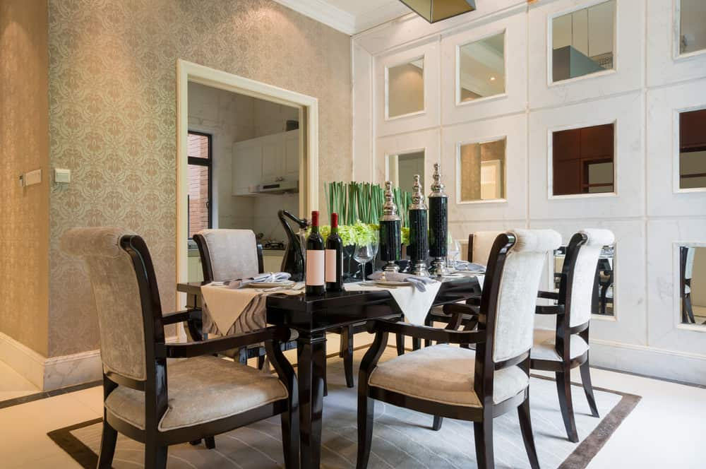 A focused shot at this dining area's classy dining table and chairs set surrounded by beautifully decorated walls.
