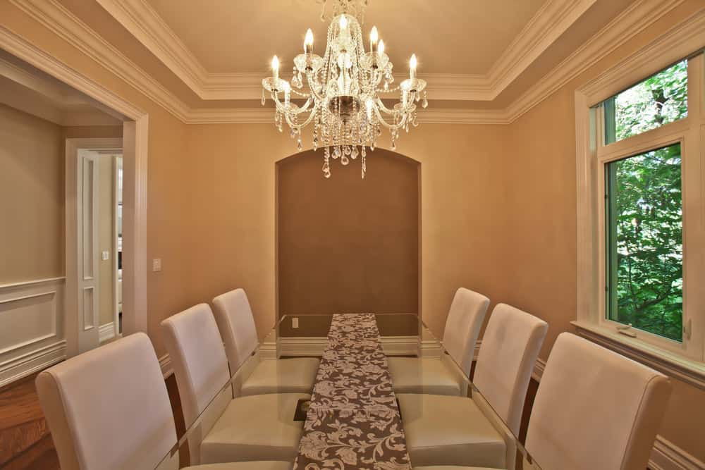 This dining room boasts a decorated glass top rectangular dining table set paired with modern chairs and is lighted by a glamorous chandelier hanging from the tray ceiling.