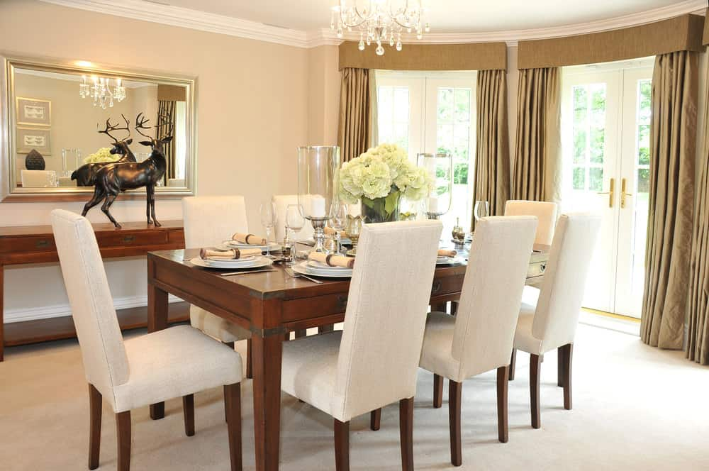 A close up look at this dining area's lovely dining table set with white chairs lighted by a charming chandelier. The area features carpeted flooring.