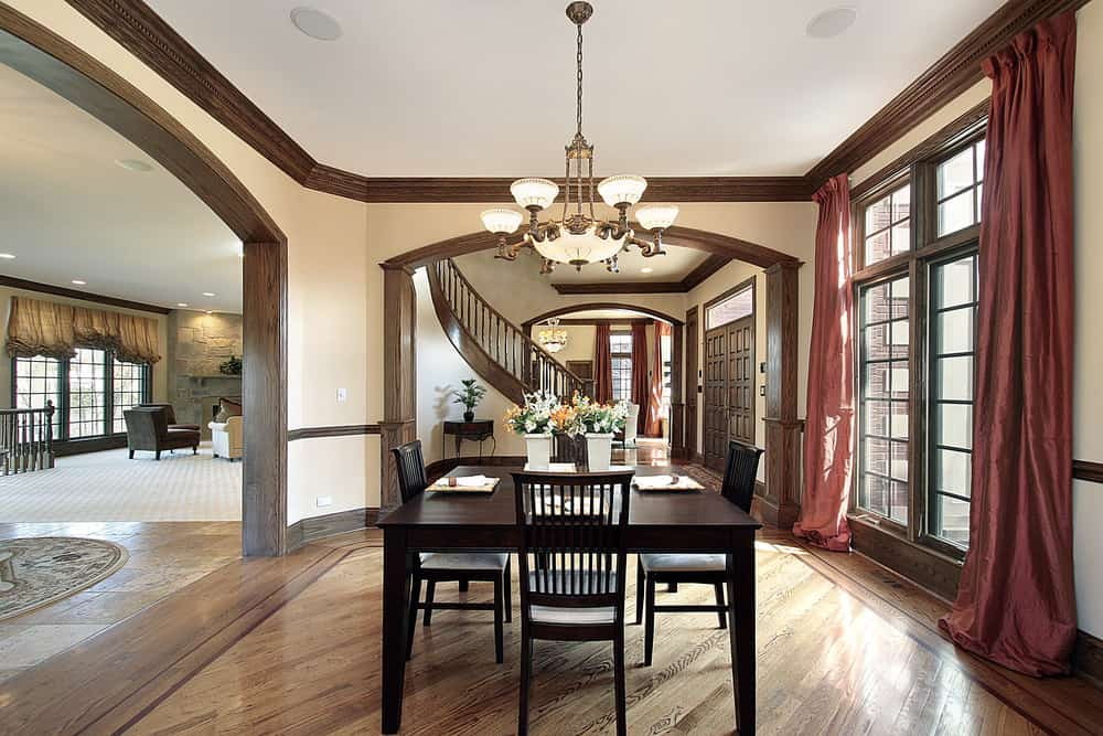 A focused shot at this dining room's square dining table and chairs set lighted by a fancy ceiling light.