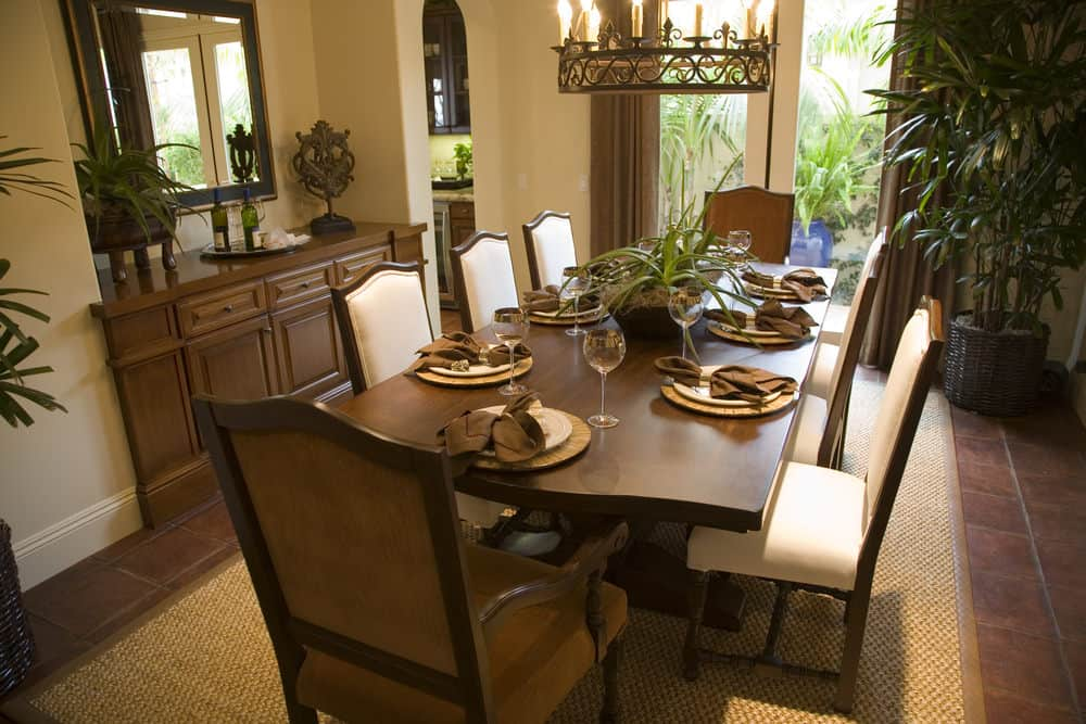 A dining area featuring a rectangular dining table set with eight seats set on a brown area rug and is lighted by a candlelights ceiling light.