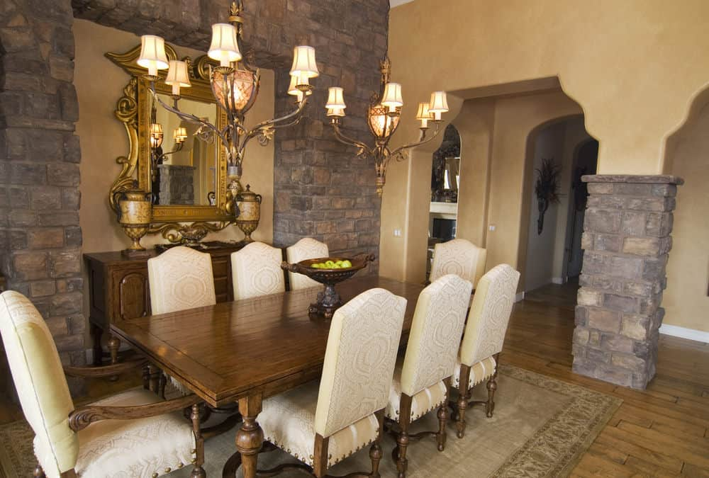 Dining area featuring a wooden dining table along with white decorated chairs set on top of an area rug covering the hardwood flooring. The table set is lighted by charming chandeliers.