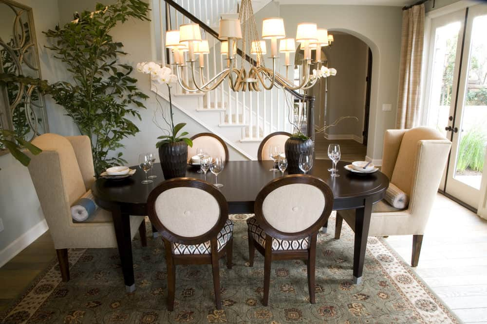 A dining room featuring an oval dining table and classy chairs lighted by a large gorgeous chandelier.