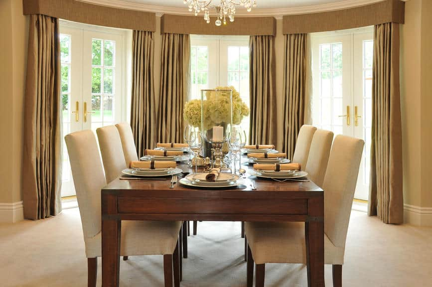 A focused look at this dining room's wooden dining table set paired with classy white seats surrounded by beige walls and is lighted by a charming chandelier.