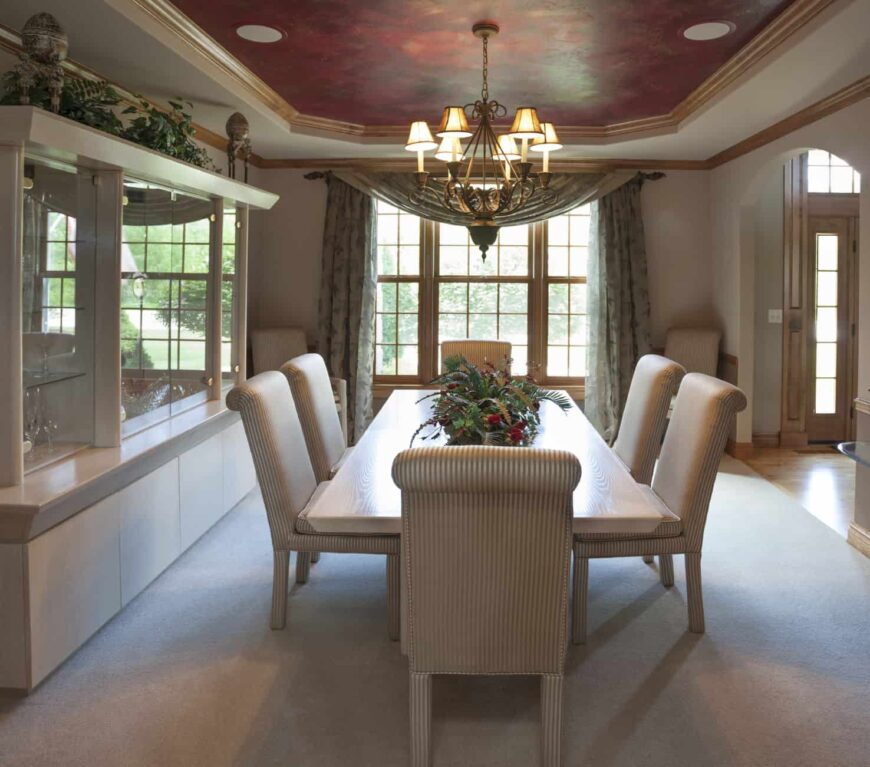 A dining room offering a classy dining table set for six, lighted by a gorgeous chandelier hanging from the stunning red ceiling.