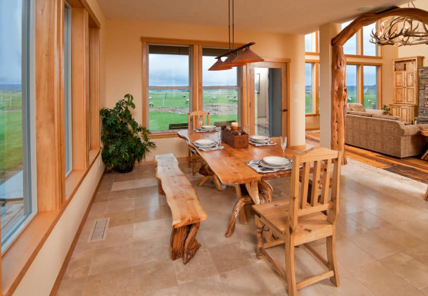 This dining room boasts a wooden dining table and chairs set situated near the home's large glass windows. The home features tiles flooring and beige walls.