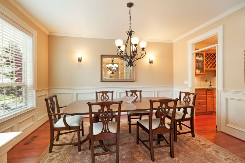 Dining room featuring a classy dining table set on top of the brown area rug lighted by a gorgeous chandelier and wall sconces.