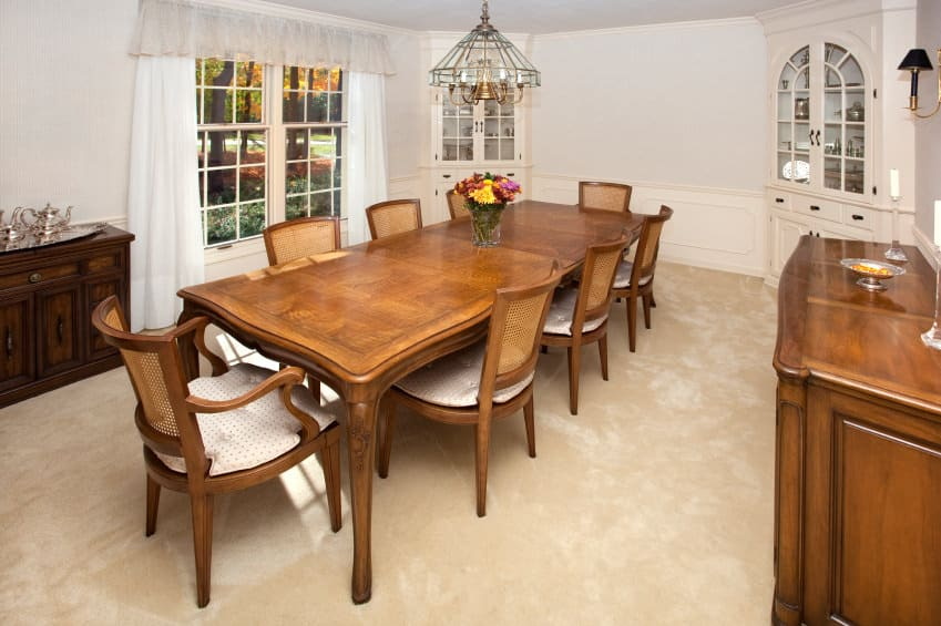A dining space featuring a wooden dining table and chairs set. The room also features fine carpet flooring.
