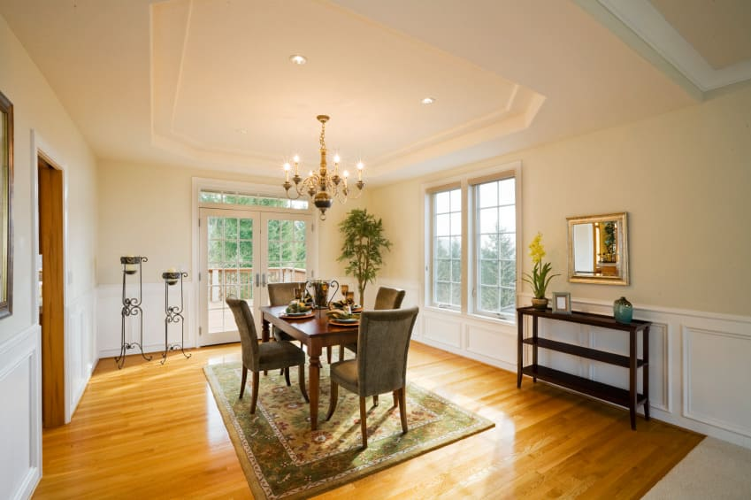 Large dining room featuring a lovely white tray ceiling and beige walls. It has a classy dining table and chairs set on top of an area rug.
