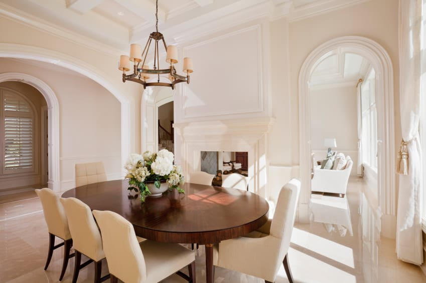 An oval dining table set with charming seats lighted by a fancy chandelier hanging from the white coffered ceiling.