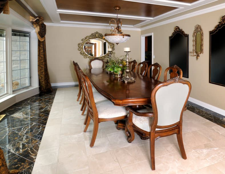 A dining room featuring a wooden dining table set under the home's stylish ceiling and lighted by a gorgeous pendant light.