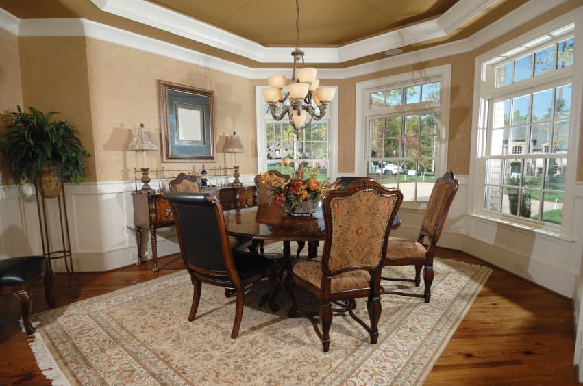 A dining room featuring a round brown dining table and chairs set on top of an area rug covering the hardwood flooring and is lighted by a gorgeous chandelier.